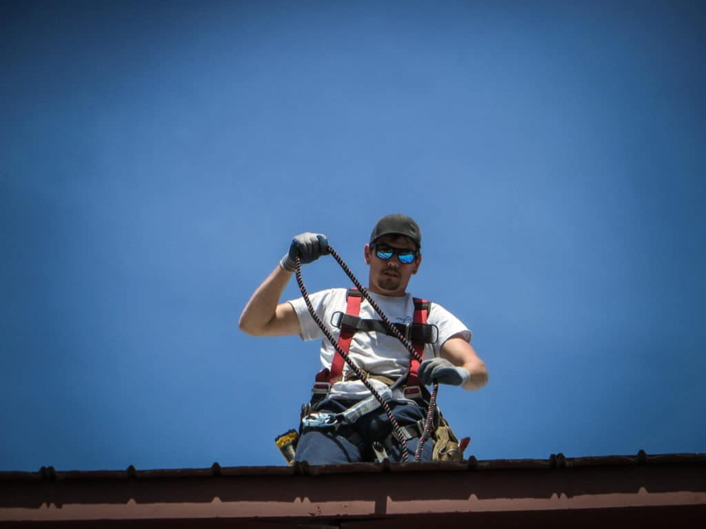 one of Markelangelo's roofers safely checks shingles